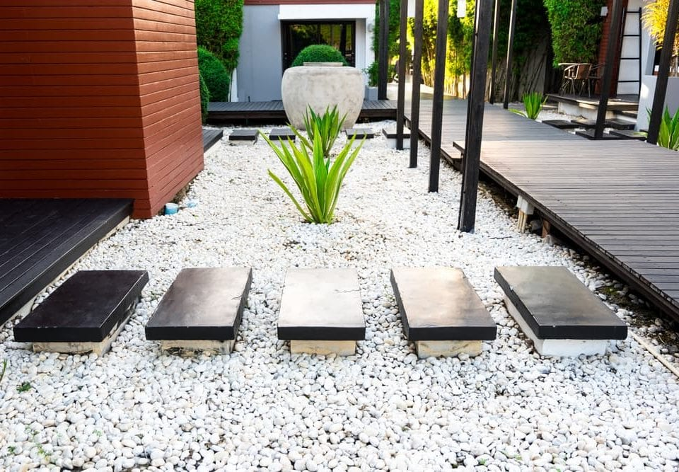 Black rocks walking way in tropical garden, Black stones garden path on white pebbles and lush green trees, Garden decoration concept