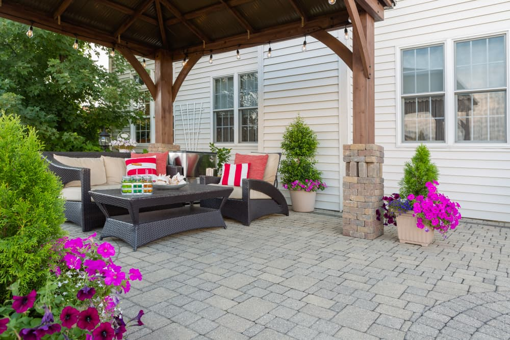 Brussel block design pavers on an exterior patio and summer living space with a covered gazebo, colourful petunias and comfortable seating